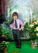 cute boy in business suit and purple shirt around flowering shru