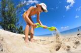 Fillette jouant dans le sable à la plage.