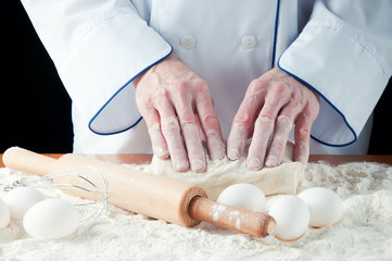 Pair of baker's hands kneading bread dough on wooden table