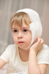 Little girl with a compress on the sore ear