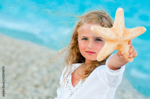 Lovely girl with starfish at the beach