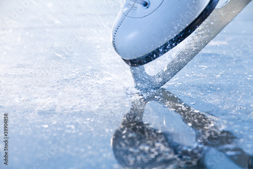 Foto op Canvas Wintersporten Woman skates braking ice, frazil flying around