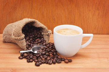Coffee cup with burlap sack of roasted beans