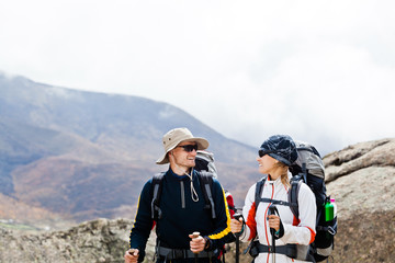 Man and woman hiking in mountains, trekking adventure