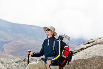 Man hiking in mountains, trekking and climbing