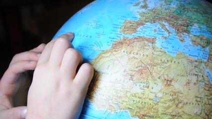 Kinderhände erforschen die Weltkugel