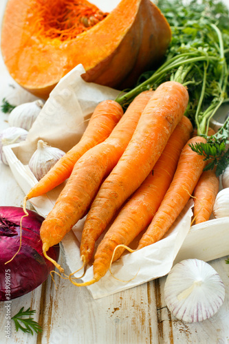 Pumpkin, carrot, garlic and red onion on white wooden background