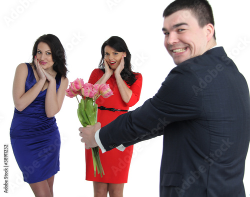 a man with a bouquet of flowers and two young women
