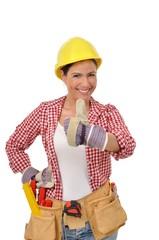 Handwerkerin mit Handschuh und Helm hält einen Daumen hoch