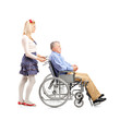 Full length portrait of a daughter pushing her dad in a wheelcha