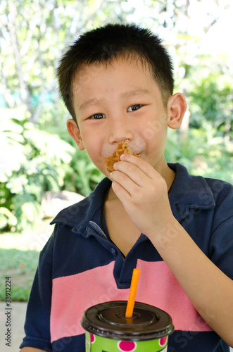 Asian boy eating muffin