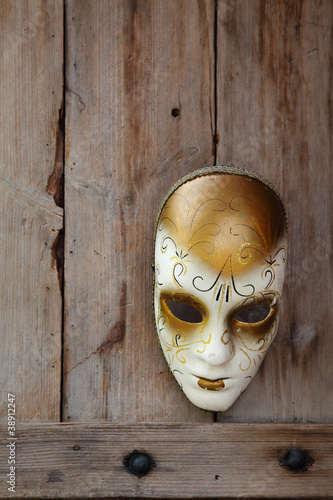 Venice carnival mask hanging on wooden door