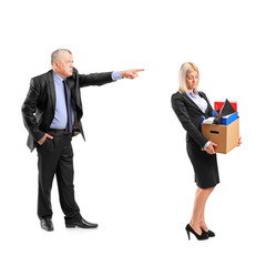 Angry boss firing a woman in a suit carrying a box of personal i