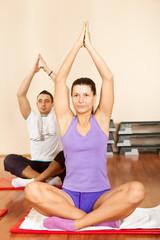 Young man and woman doing yoga