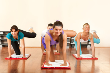 four people is doing exercises in fitness club
