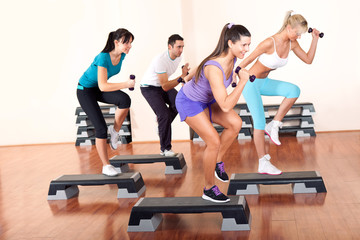 young people stepping with dumbbells