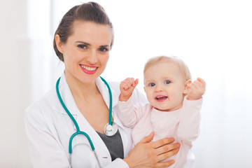 Portrait of pediatrician doctor with smiling baby