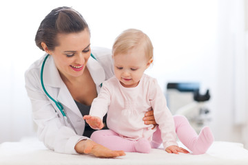 Cheerful baby high five to pediatrician doctor