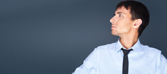 Portrait of relaxed business man against grey background.