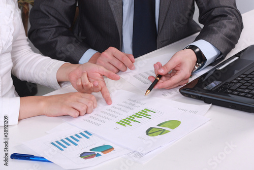 business partners hands over papers discussing them