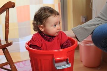 Kind in einem Plastikeimer