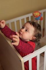 Kind in seinem Kinderbett
