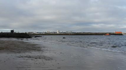 waves breaking and Aberdeen skyline Scotland