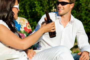 Couple drinking beer in summer