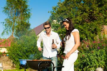 Paar beim Grillen im Garten im Sommer
