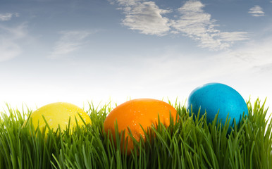 Three colorful Easter eggs in the grass under blue sky