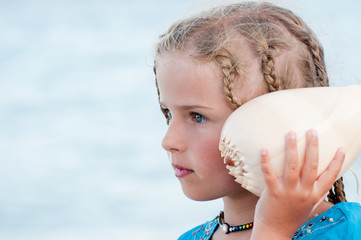Lovely girl with shell at the beach