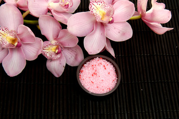 bath salt in a bowl and flowers of orchids on mat