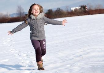 girl running on snow in park