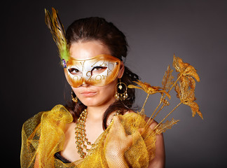 Young woman in carnival costume with mask .