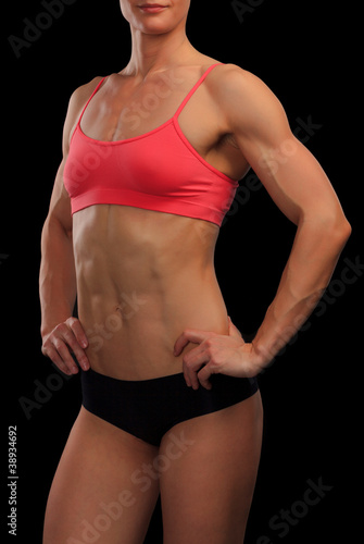 Female fitness bodybuilder posing against black background