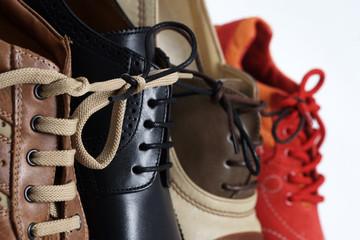 Verschiedene Schuhe aneinandergeschnürt, Symbol für Bindung