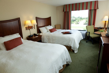 Empty hotel or mtotel room with two beds