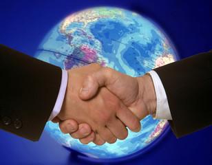 Zwei Geschäftsmänner geben sich vor einem Globus die Hände