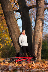 Woman cyclist relaxing in autumn nature