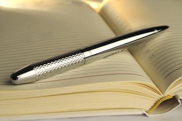 silver pen on notebook