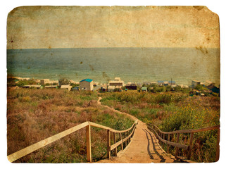 A staircase leads down to the sea. Old postcard.