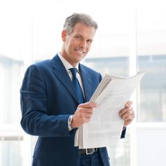 Satisfied businessman read newspaper