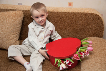 Adorable child boy with bouquet of tulips and red heart