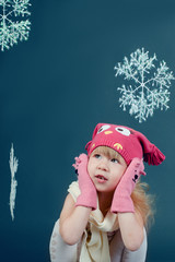 Girl in winter hat and gloves framed by snowflakes