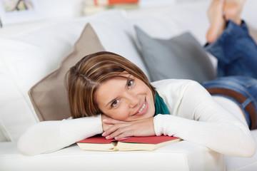 entspannte frau mit buch auf dem sofa