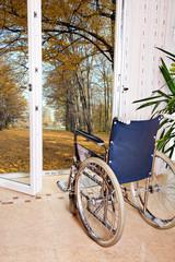 Rollstuhl steht vor offenen Fenster