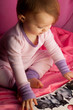 Child viewing a book in a pink tent fort