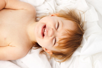 Happy child laughing and laying in white sheets