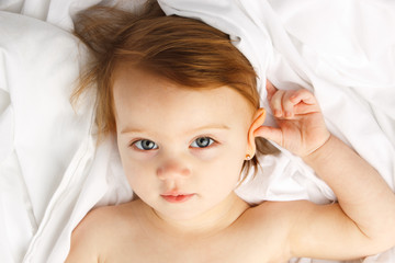 Beautiful little girl staring up while laying on white sheets