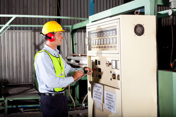 industrial technician writing down machine temperature